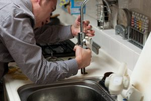 Plumber fixing a kitchen sink.