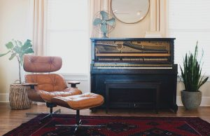 an upright black piano and a brown chair in a room