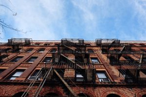 A red brick NYC rental real estate with metal fire staircase escape