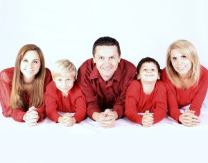a family dressed in red clothes happy after moving with children to Manhattan