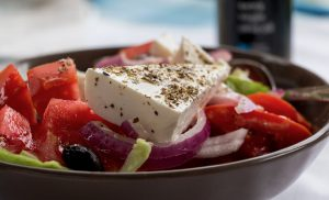 A brown plate of salad made of feta cheese, onion, olives and tomato you can enjoy after moving to Bay Ridge