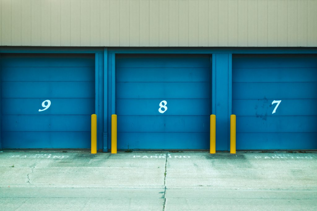Three storage units with blue doors that roll up and numbers 7, 8, 9 written on each