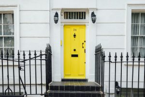 yellow house door - things to do before moving into a new home