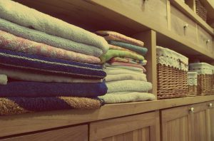 A brown shelf in a bathroom, presumably, can be seen. On the one side, we have many different towels stacked one onto another. They are positioned in two rows. On the other side of the shelf, we have three baskets one next to each other.