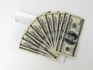 Twelve 100-dollar bill banknotes on a white surface.