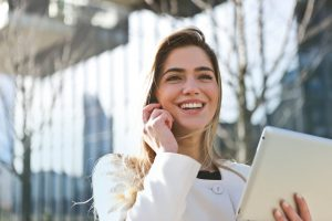 A blonde woman dressed in a white jacket with a black collar smiling. She is holding a phone in her left hand, and a white tablet in her right hand. She might be having a video call. Before moving from South Africa to NYC it is important to attend video interviews.
