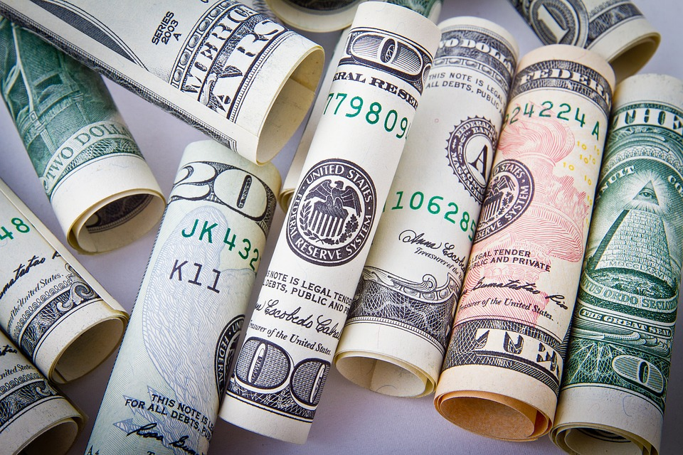 We see a lot of rolled up dollar bills in the picture. There are ways to save money in the Big Apple that will leave you with a nice amount of savings.
