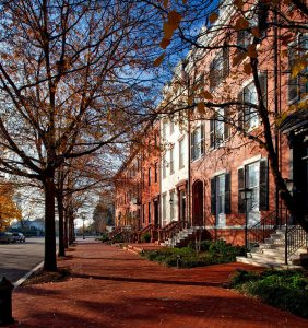 A row of brownstones on a street. In front of them, trees with yellow leaves can be seen, which signs that it is the autumn season. Brownstones are a logical choice for people buying a home in Park Slope.