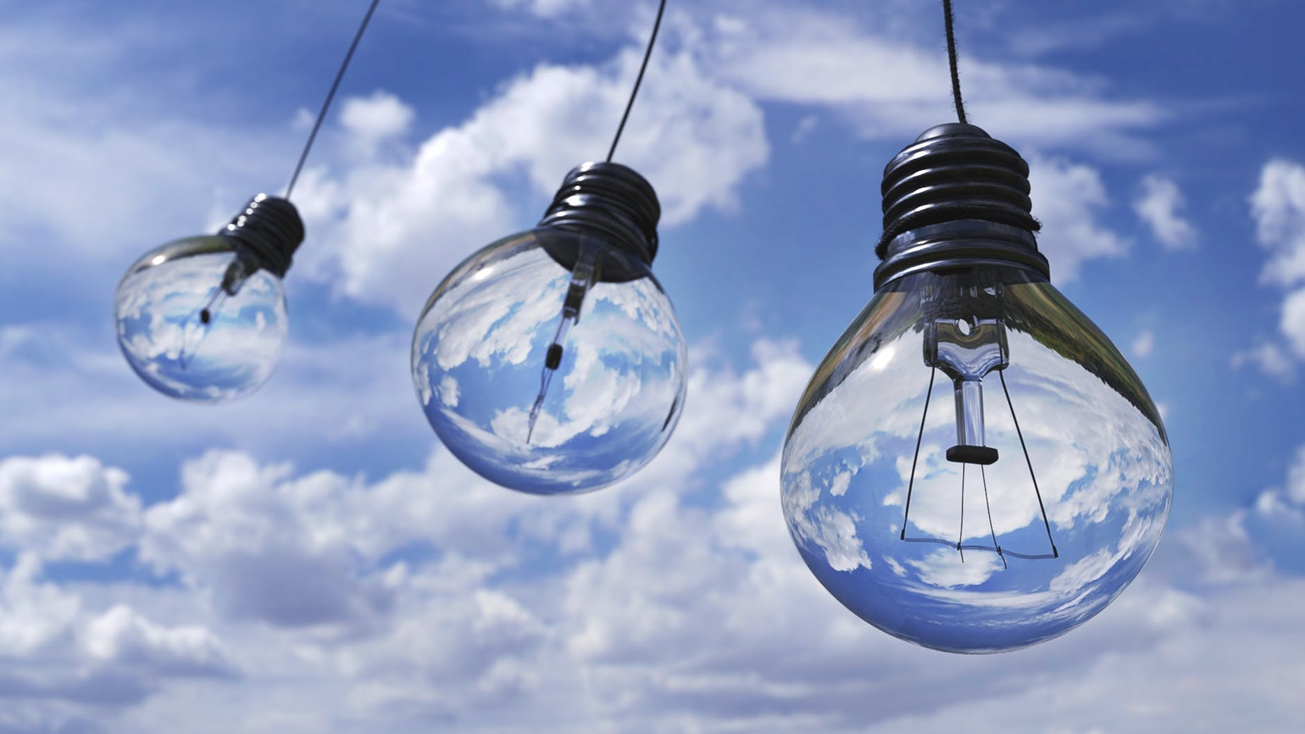Three light bulbs hanging. We see the sky behind them. Glass is very delicate, and you should learn how to pack fragile items such as this one.