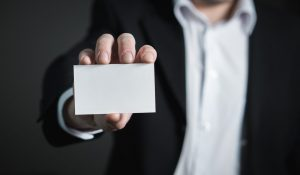 A close up of a man in suit holding a blank paper.