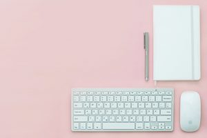 A white keyboard, mouse and a notebook on a pink surface.