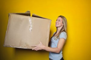 A blonde woman holding a big cardboard box and standing in front of a yellow background. The woman is smiling and wearing a grey shirt.