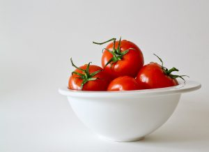 A white bowl that contains four red tomatoes. The bowl is placed on a white surface and in front of a white wall.