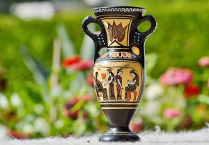 A black and yellow clay vase with Egyptian symbols, placed on a white surface. This vase is expensive, so packing antiques by yourself can bring a financial loss.