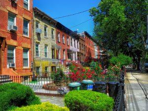 A row of brownstone houses in the daylight.
