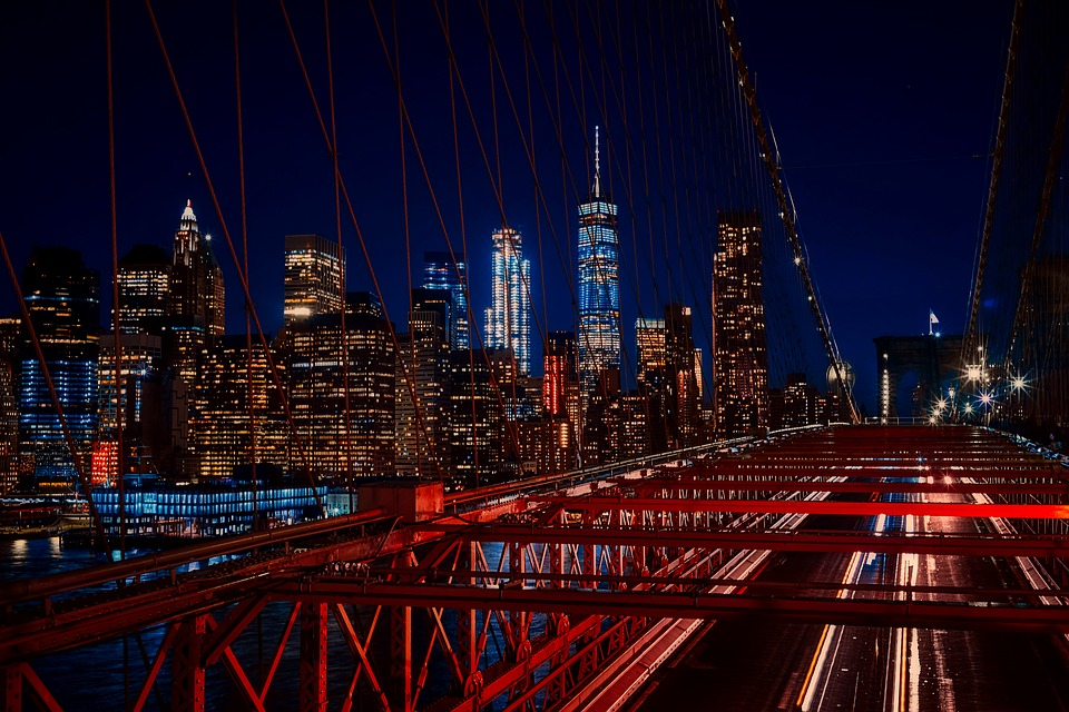 An aerial view of the Brooklyn bridge and New York City at night. Just across the bridge are the best places to buy a house in Brooklyn.