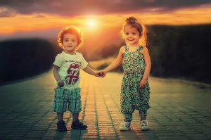 A picture of a boy and a girl holding hands.