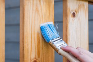 A close-up of a hand holding a blue brush, and painting a wooden fence.