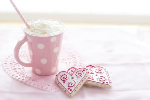 A pink mug with white polka dots