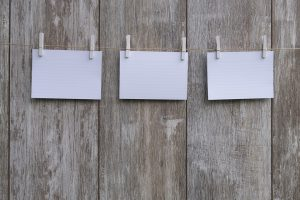 Three pieces of paper on a string, which are necessary when decluttering and summer storing.