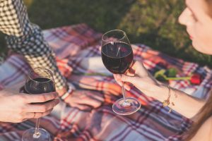 People holding wine glasses on a blanket.