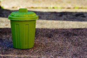 A green garbage bucket on the ground, to help you clean your apartment with ease.