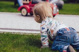 A close up of a boy crawling in a backyard.