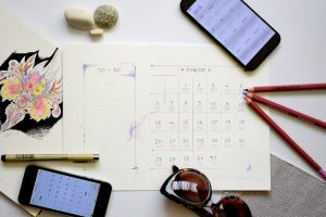 Calendar with pens and mobile phone on a desk.
