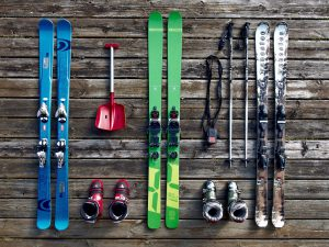 Three pairs of skiis on a wooden surface.