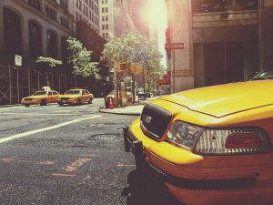 Three yellow taxis on a street in New York.