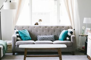 Grey couch in living room with blue pillows.