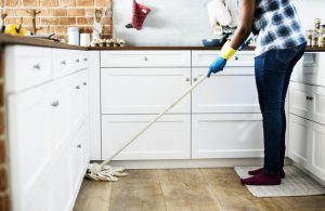 Woman cleaning kitchen floors.