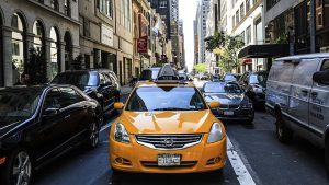 NYC streets with cars and a yellow cab.