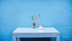 Blue wall and a table with a vase.
