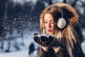 Woman holding snow in her hands.