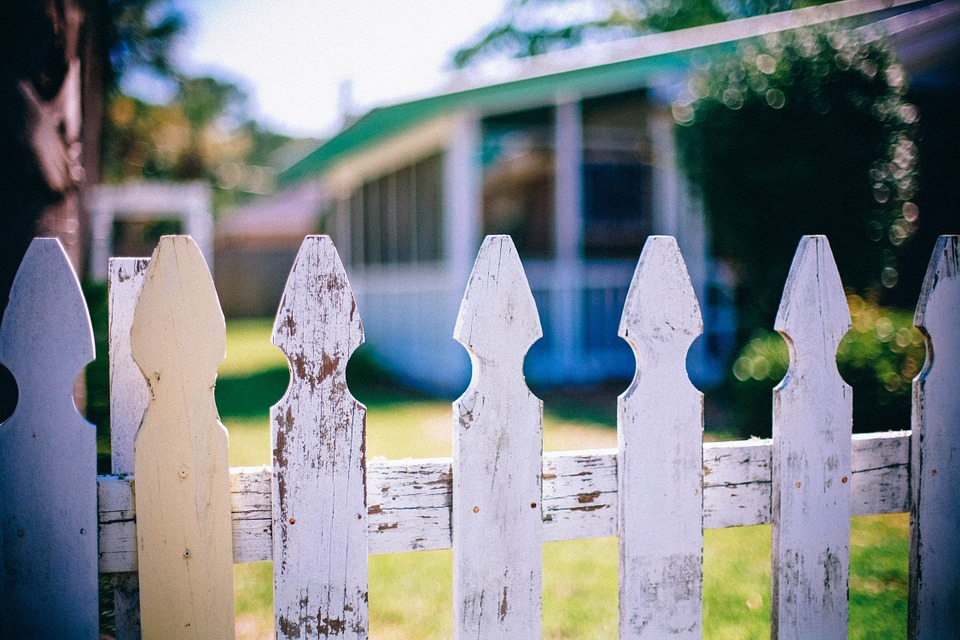 White picket fence in front of a house.