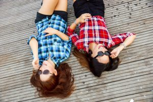 Two girls laying on wooden floor.