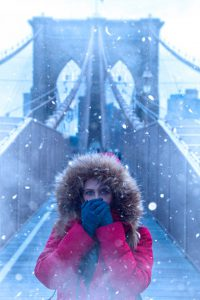 A girl on a Brooklyn bridge in snow