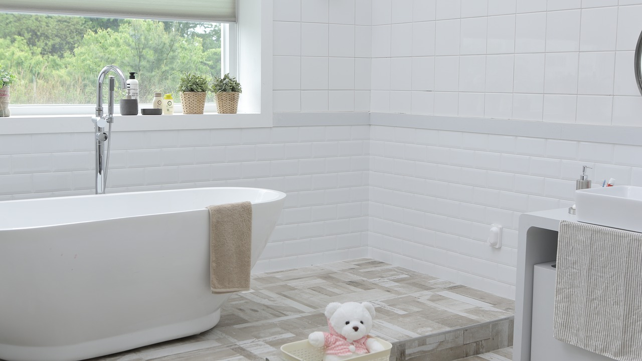 A part of a bright, white bathroom with a bathtub