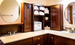A brown bathroom counter and cabinets. Think about storage when you remodel a small bathroom.