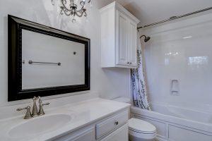 A white bathroom with a black mirror.