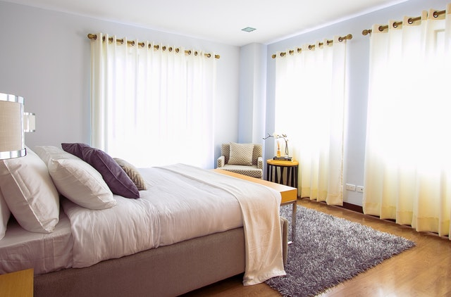 Bedroom with curtains over its big windows and a gray carpet.