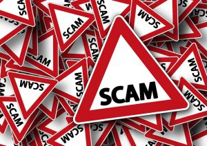 A pile of road signs that say ''SCAM''. Among the risks of hiring cheap movers is the possibility of getting scammed.