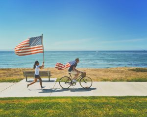 One girl running while holding a USA flag and a boy doing the same while riding a bicycle