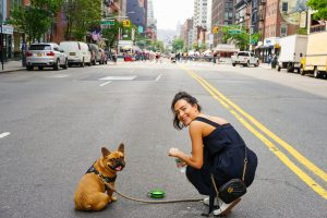 a girl with a pet on the street after finding cheapest housing in NYC for newcomers