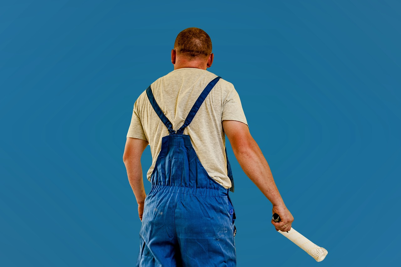 House painter standing in front of a blue wall