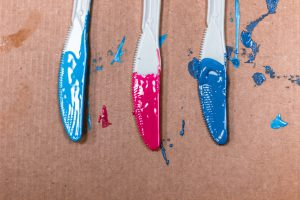 plastic knives covered in paint on a piece of cardboard