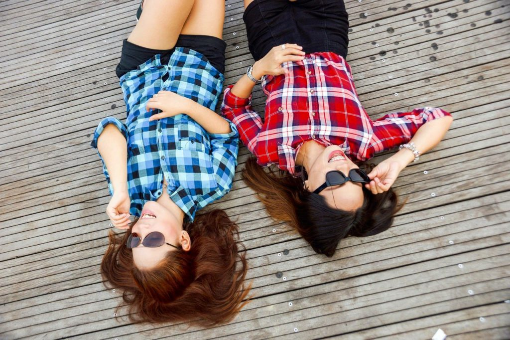 two women laying on the ground in summer clothes