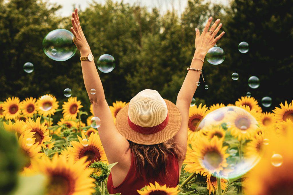 Woman wearing a sun hat in a sunflower field